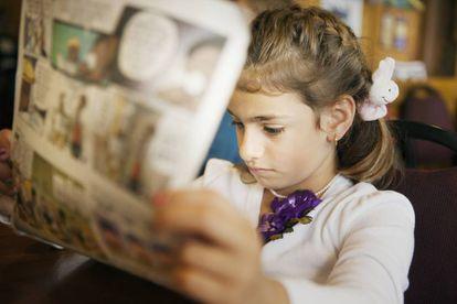 Una niña lee un cómic.