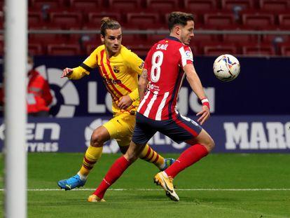 Saúl y Griezmann durante un partido entre el Atlético y el Barcelona.