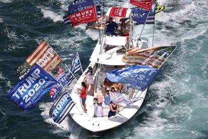 Seguidores de presidente Donald Trump durante un desfile hasta la orilla de la casa del exmandatario en Mar-a-Lago, en West Palm Beach, Florida.