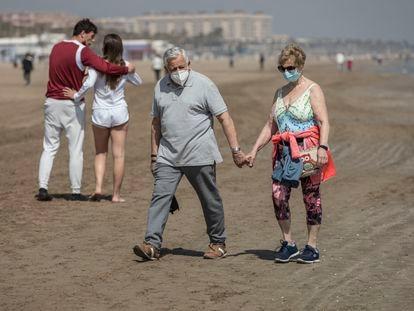 Dos personas caminan por la playa de la Malvarrosa, en Valencia, en marzo.