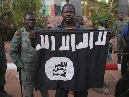 Agentes maliense muestran una bandera yihadista hallada en un hotel de Bamako, atacado en noviembre de 2015.
