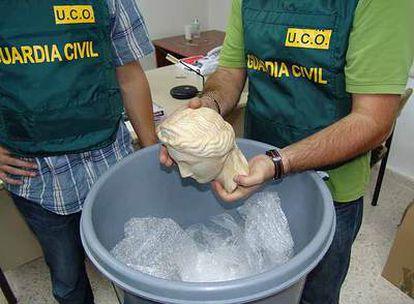 Dos agentes de la Guardia Civil muestran una de las esculturas halladas en un cubo de basura.