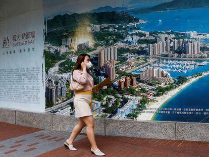 Una mujer pasa ante el anuncio de una promoción de viviendas construidas por Evergrande en Hong Kong