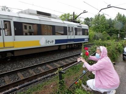 Una mujer coloca flores en el lugar del atropello ferroviario de dos mujeres en Torrelavega.