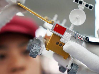 Un trabajador inspecciona un modelo miniatura del vehículo lunar para la sonda china Chang'e 4, en una fábrica en Dongguan, China.