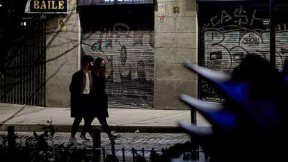 Dos personas pasan por delante de un comercio cerrado el 17 de enero en Madrid.