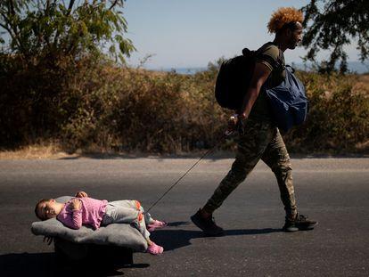 Un migrante arrastra a un bebé por una carretera en Lesbos (Grecia).