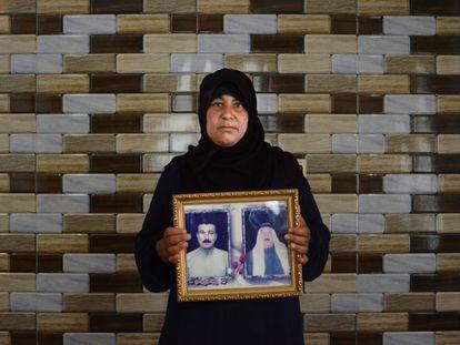 Um Omar sostiene un cuadro con las fotografías de su marido Muntadar (izquierda), desaparecido en 2016, y de su padre fallecido.