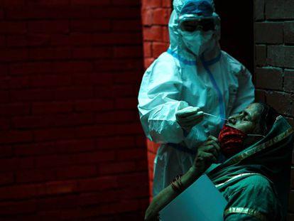 Un sanitario realiza una prueba PCR para detectar la covid-19 en una ciudadana en Nueva Delhi (India).