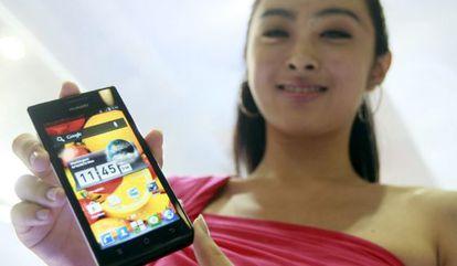 Una azafata muestra un modelo de teléfono inteligente.