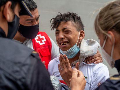 Varios agentes y voluntarios de Cruz Roja atienden a un menor en Ceuta.
