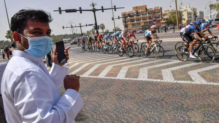 Un aficionado con mascarilla observa el paso del pelotón durante el UAE Tour antes de que la carrera se suspendiese por el coronavirus.