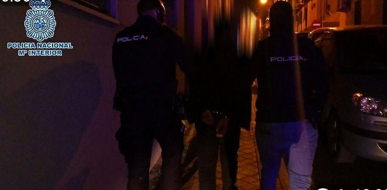 Dos agentes conducen al detenido, un conocido alunicero.