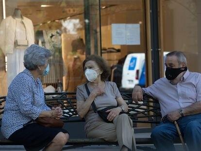 Tres personas con mascarillas conversando en un banco, en Madrid, el pasado miércoles.