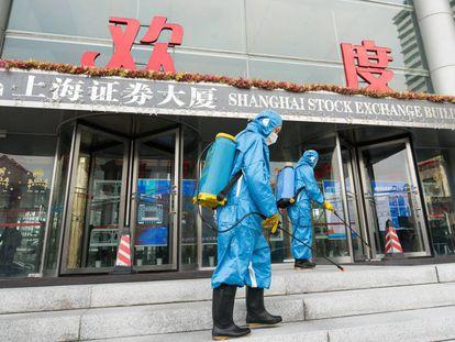 Técnicos sanitarios desinfectan la entrada principal de la Bolsa de Shangái.