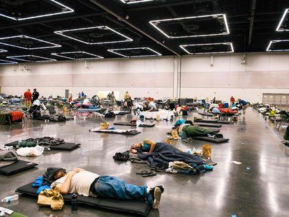 Vecinos de Oregón, en Portland (EE UU), este lunes en uno de los centros con aire acondicionado que se han preparado por la ola de calor para que la gente pueda descansar en un espacio fresco.