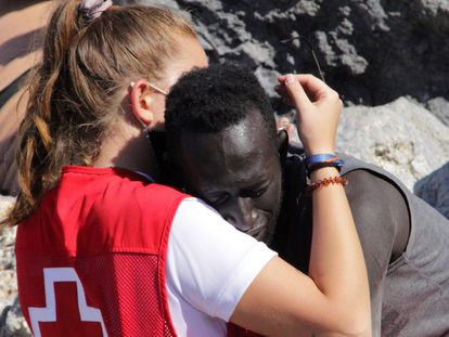 Una trabajadora de la Cruz Roja y uno de los migrantes que lograron cruzar a Ceuta el martes se abrazan.