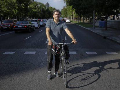 José Rossi, miembro de la Plataforma Carril Bici Castellana posa con su bici en el centro de la Castellana en Colón, Madrid.