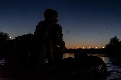 Un hombre haitiano y su hijo cruzan el Río Bravo desde Ciudad Acuña (Coahuila) hasta Del Río (Texas), este jueves.