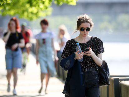 Una chica consulta su teléfono mientras pasea en Moscú.