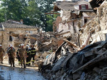 Bomberos y soldados italianos caminan entre las ruinas durante una operación que tiene el objetivo de reabrir la carretera de Rio, una pequeña aldea cerca de Amatrice.