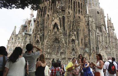 Grupos de turistas frente a la Sagrada Familia en Barcelona.