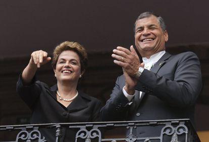 Los presidentes de Brasil, Dilma Rousseff (izq) y de Ecuador, Rafael Correa saludan desde un balcón en Quito.