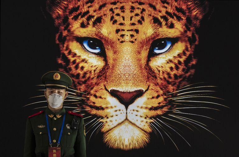Un oficial de policía vigila ante un cartel el pasado 23 de enero en Pekín.