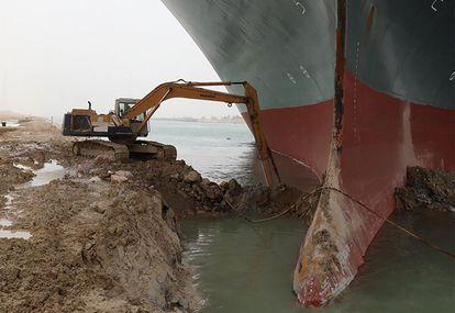 Una excavadora retira tierra alrededor del buque.