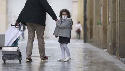 Una niña pasea con un adulto, el lunes 20 de abril en el centro de San Sebastián / Javier Hernández