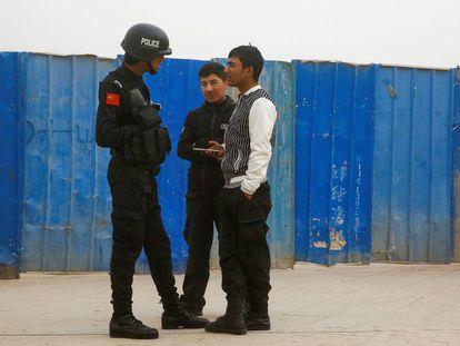 Un policía chino habla con dos ciudadanos en Kashgar (Xinjiang), en marzo de 2017.