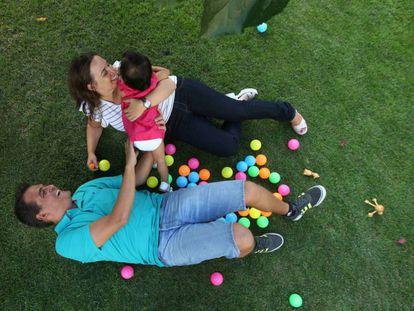 Una pareja juega con su hijo en adopción.