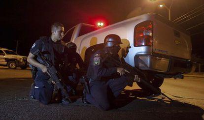 Agentes de la policía mexicana se posicionan detrás de vehículos durante el tiroteo en la prisión de Ciudad Juárez.