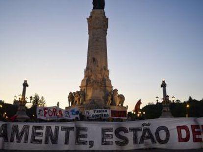 """Manifestantes sujetan una pancarta que reza: """"Obviamente, estáis cesados"""" en la plaza del Marqués de Pombal en Lisboa."""