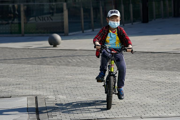 Un niño monta en bici con una mascarilla en Pekín.
