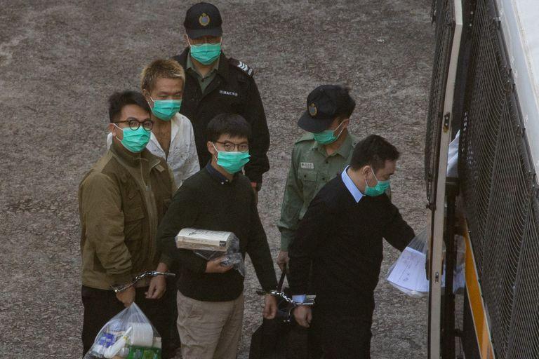 Joshua Wong, en el centro, es trasladado por las autoridades este miércoles tras conocer su sentencia, en Hong Kong.