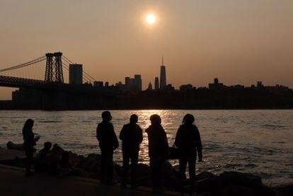 Un grupo de personas observa el atardecer desde Manhattan (Nueva York) donde se observa la bruma.