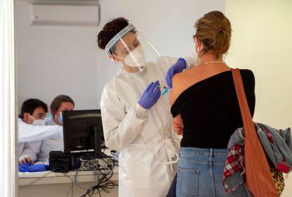 Personal sanitario vacuna a una mujer contra la covid en el recinto del antiguo hospital Son Dureta, este martes en Palma de Mallorca.