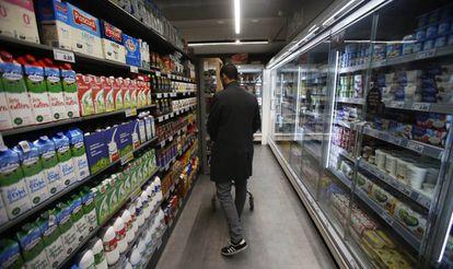 Un consumidor en la línea de productos lácteos de un supermercado en Madrid.
