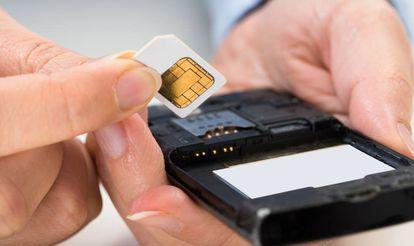 Una persona introduce una tarjeta SIM en un teléfono móvil.