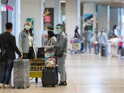 Varias personas protegidas con mascarillas y pantallas protectoras, en la terminal T1 del Aeropuerto Adolfo Suárez Madrid-Barajas el 1 de julio.