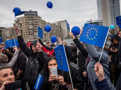 Ciudadanos rumanos se manifiestan portando banderas de la Unión Europea, en marzo en Bucarest.