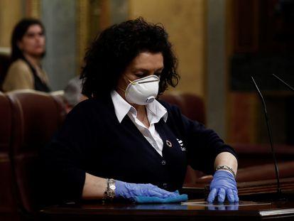 Una ujier desinfecta un atril en el Congreso de los Diputados, en marzo de 2020.