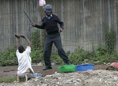 Una mujer suplica a un policía que no la golpee con la porra en la barriada de Mathare.