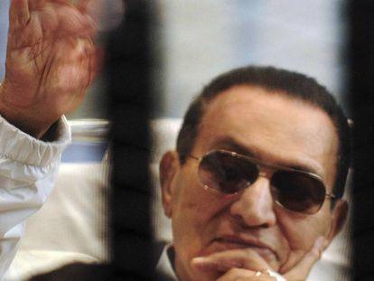 Hosni Mubarak saluda a sus partidarios enjaulado en una sala de audiencias en la academia de policía de El Cairo, en abril de 2013