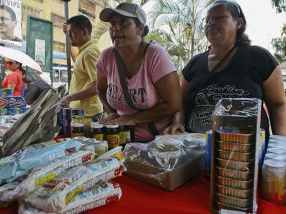 Un par de mujeres compran comida en un mercado estatal de Caracas.