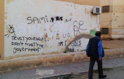 Un ciudadano pasa al lado de un graffiti que proclama: 'Confía en ti, no en el Gobierno'.
