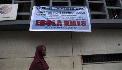 Una mujer pasa bajo un cartel con recomendaciones para hacer frente al ébola en Freetown (Sierra Leona).