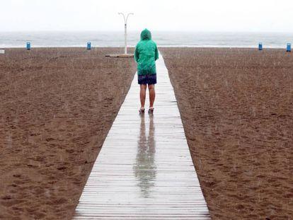 Una mujer contempla la playa de la Malvarrosa bajo la lluvia durante la mañana del domingo.