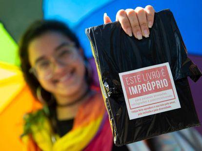 Una mujer muestra uno de los ejemplares regalados por el youtuber el sábado en la Bienal de Río.